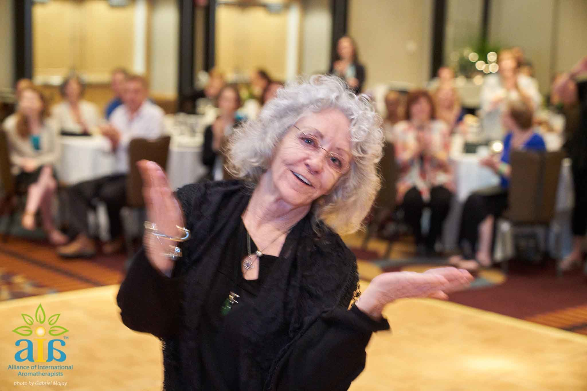 Sylla Recognized for Outstanding Contributions   At the Alliance of International Aromatherapists Conference this past August, many friends and colleagues had the pleasure of seeing Sylla win win this year's Outstanding Contributions Award. Thanks to our student's idea, we managed to get it on video. Check out our Facebook Live Video and see what it was like to be in the room during Sylla's second most happiest moment of her life. You'll also learn what her most happiest moment has been. Here is Sylla's response: I finally feel seen. I have worked 40 years in this field and accomplished a lot, and I feel like for the first time my story was told and I was honored for my efforts. When I started teaching long ago it was my dream to make a difference in the world of aromatherapy. As I went along and created Atlantic Institute of Aromatherapy, I had more ideas, wrote a book, hooked up with safety experts, went to Purdue and France chasing my dream and teaching others along the way.  After 9/11, I was moved to act, the UAE, Inc. formed organically and was supported by the community. Now the organization has been reinstated for the future generations! Getting the award and listening to the 11 mins of accomplishments was like a dream come true, I amazed myself(!) and felt completely recognized for the first time ever in my aroma career.  Watching the video later I realized there was this slideshow playing behind me, little did I know the care that Lora Cantele took to make the presentation. As the conference went on I learned how much some wanted me to win this, and how much they felt I deserved it long ago. I also learned that many did not even know all I have done in my 40 years. I feel completely seen and heard for the first time. With this honor, I feel that I leave a good legacy and hope to inspire others. I am so glad I was alive to say this! I have never felt so loved, honored and appreciated, in my life. I lovingly accept all the recognition and feel like my cup is overflowing again.   Thank you everyone who voted for Sylla. We hope to see you at the next Alliance of International Aromatherapists Conference in 2019!